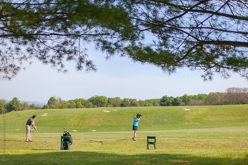Golf Driving Range: Man and Woman Practice Hitting Balls by Brian McEntire for Stocksy United
