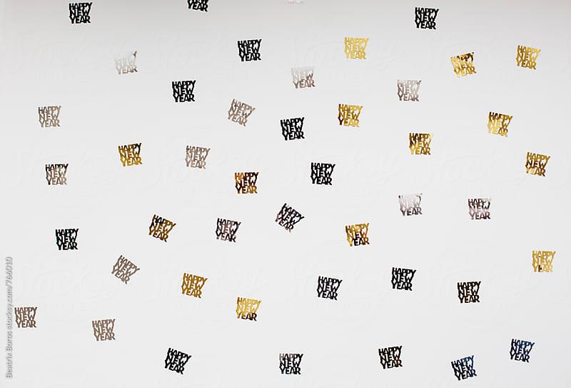 Randomly arranged happy new year confetti on white by Beatrix Boros for Stocksy United
