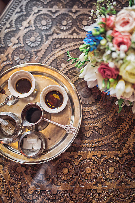 Coffee and flowers on a woden coffee table by Maja Topcagic for Stocksy United