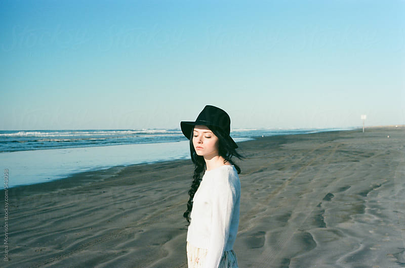 Portrait of a Young Woman Soaking in Sunshine on the Beach by Briana Morrison for Stocksy United