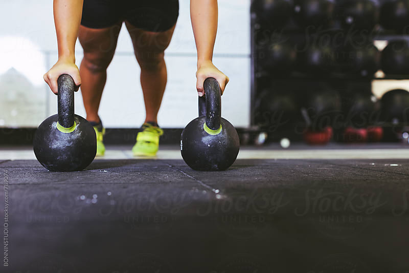 Closeup of a woman working out with kettle bells in a gym. by BONNINSTUDIO for Stocksy United