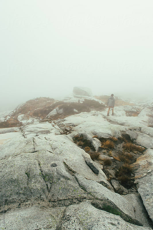 Young Man Walking Along Granite Outcrop Through Fog by Luke Mattson for Stocksy United