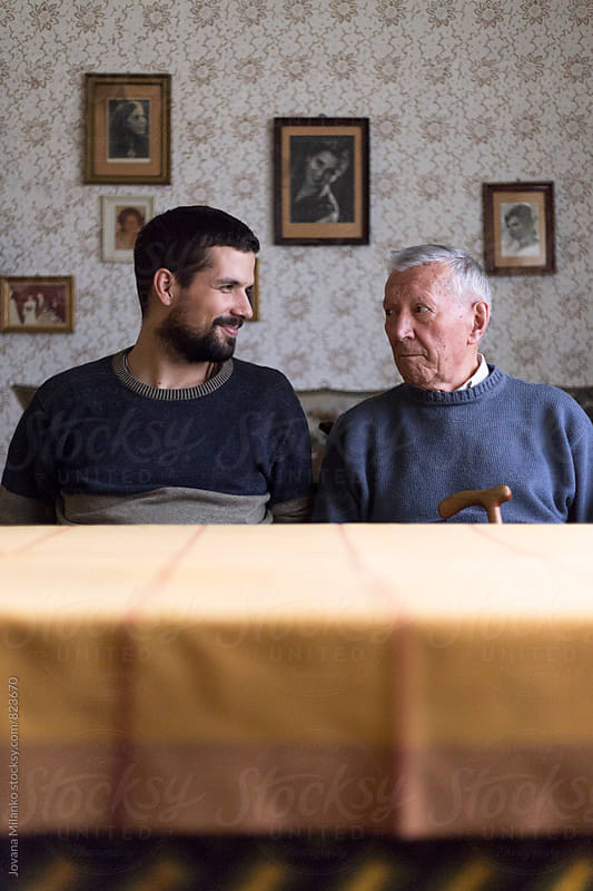 Grandpa and his kin looking at each other, sitting at the table in the living room  by Jovana Milanko for Stocksy United