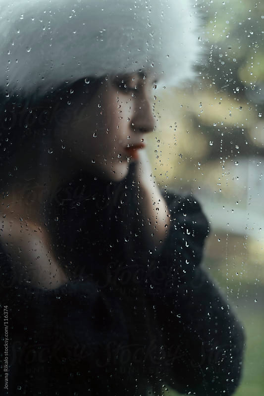 Girl standing behind the window during rain by Jovana Rikalo for Stocksy United