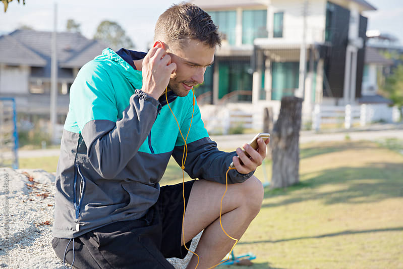 Handsome young man listening to music on his smartphone after a run in the street  by Jovo Jovanovic for Stocksy United