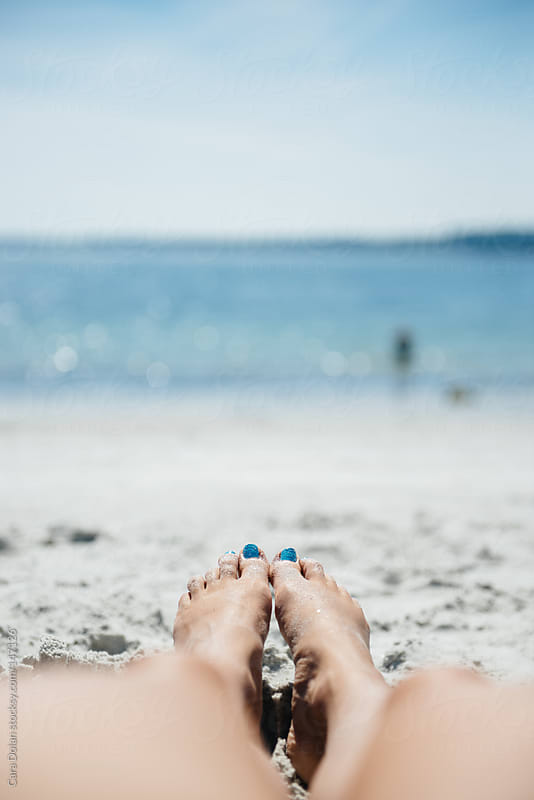 Woman's legs on a sandy beach in summer by Cara Dolan for Stocksy United