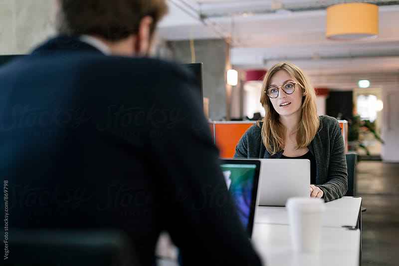 Buinesswoman talking with male coworker by VegterFoto for Stocksy United