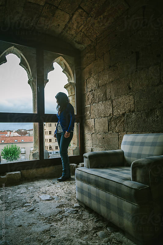 Young Woman Looking Through a Medieval Window by VICTOR TORRES for Stocksy United