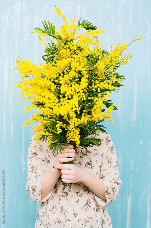 Woman hiding her face with a bouquet of yellow flowers. by BONNINSTUDIO for Stocksy United