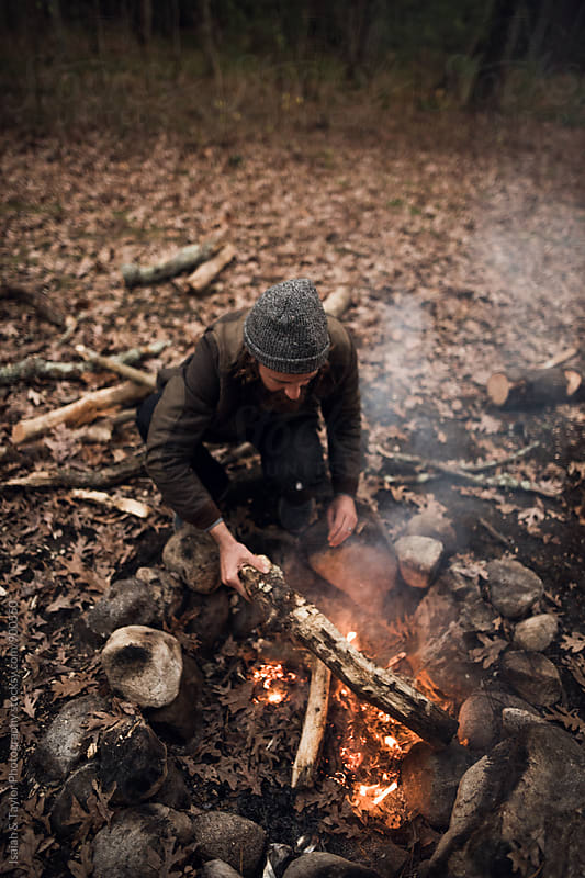 Man starting campfire by Isaiah & Taylor Photography for Stocksy United