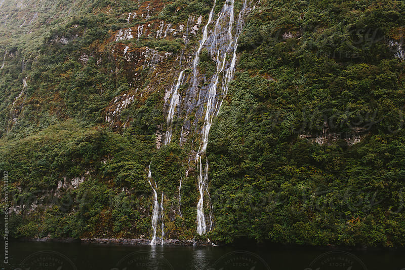 waterfall in fjord by Cameron Zegers for Stocksy United