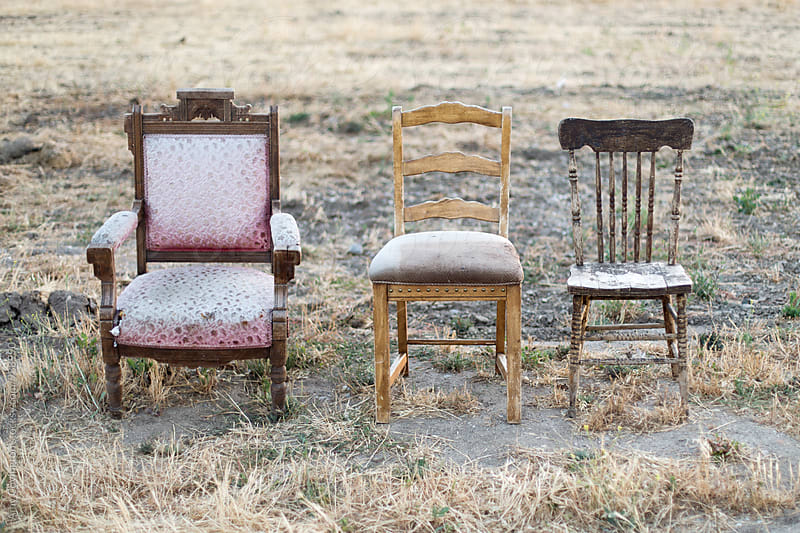Three antique chairs in a field by Amy Covington for Stocksy United