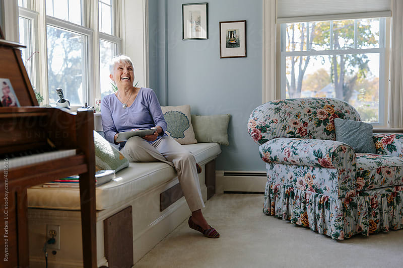 Senior Woman working on mobile tablet at Home by Raymond Forbes LLC for Stocksy United