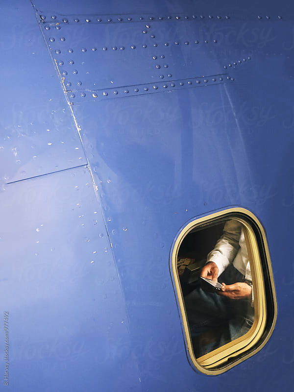 Man Using His Phone on a Plane by B. Harvey for Stocksy United