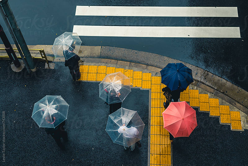 People Standing In The Rain In The City by Leslie Taylor for Stocksy United