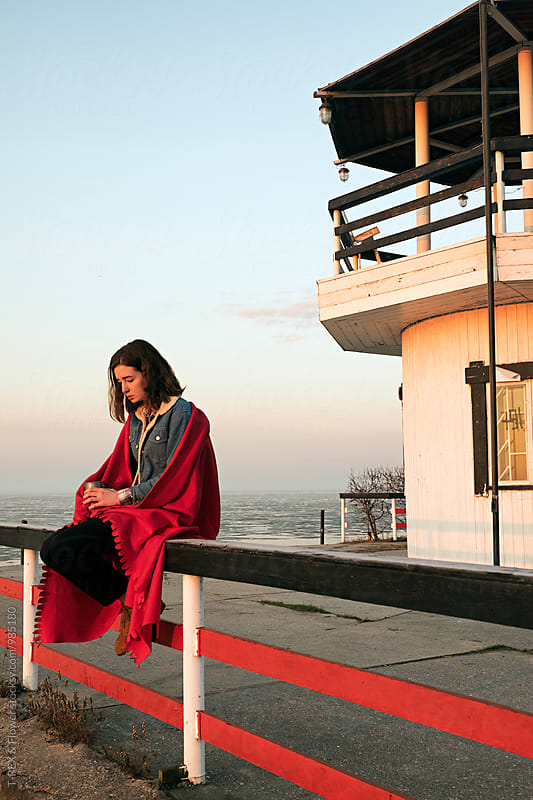 Sad girl in red blanket with hot drink against of light house by Danil Nevsky for Stocksy United