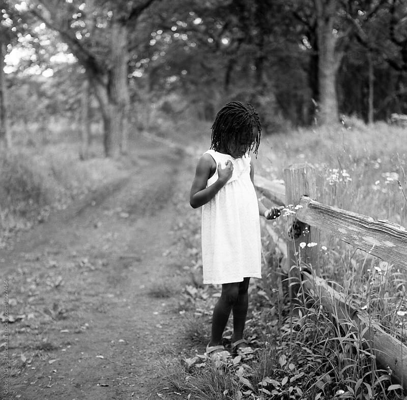 Black girl looking at flowers in a forest by Gabriel (Gabi) Bucataru for Stocksy United