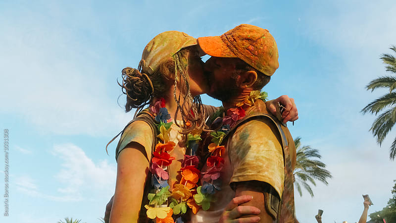 Man and woman covered with colorful holi kissing each other by Beatrix Boros for Stocksy United