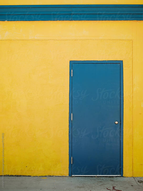 Blue door on a yellow wall by Joseph West Photography for Stocksy United