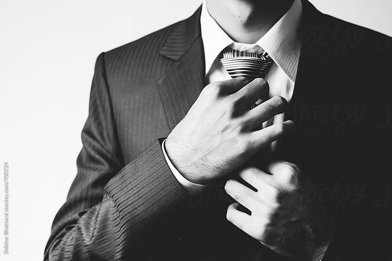 Man on a suit making adjusting his tie. by Shikhar Bhattarai for Stocksy United