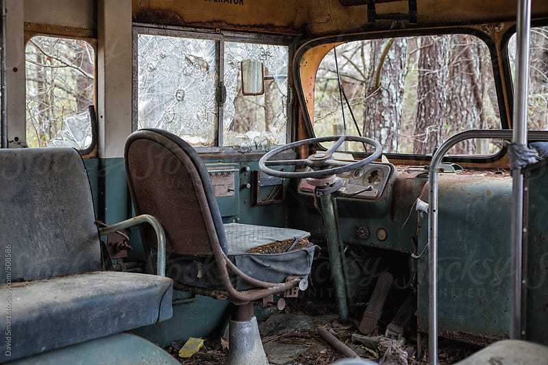 Driver's seat in an abandoned decaying school bus with broken windows by David Smart for Stocksy United