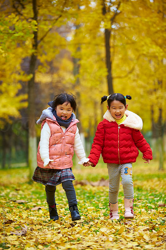two lovely asian girl having fun in the autumn woods by cuiyan Liu for Stocksy United