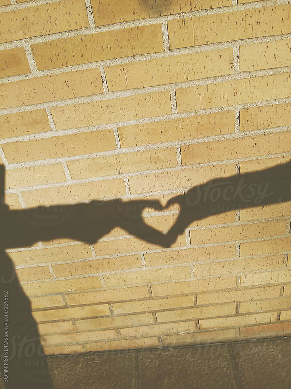 Couple making heart shadow on a brick wall. by BONNINSTUDIO for Stocksy United