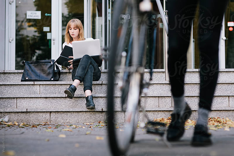 Woman sitting on building stairs and using computer by VegterFoto for Stocksy United