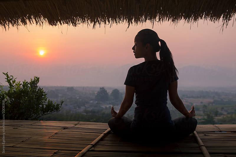 Woman meditating with view of rising sun over the mountains by Soren Egeberg for Stocksy United