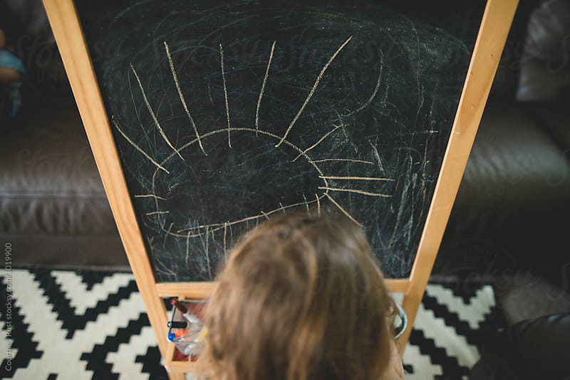 Girl drawing a creature on a chalk board  by Courtney Rust for Stocksy United