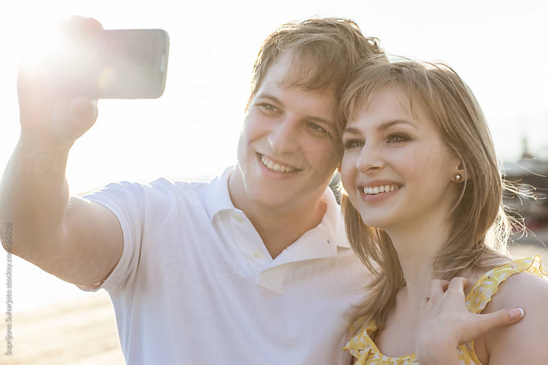 Dating young couple in love taking a picture of themselves by Suprijono Suharjoto for Stocksy United