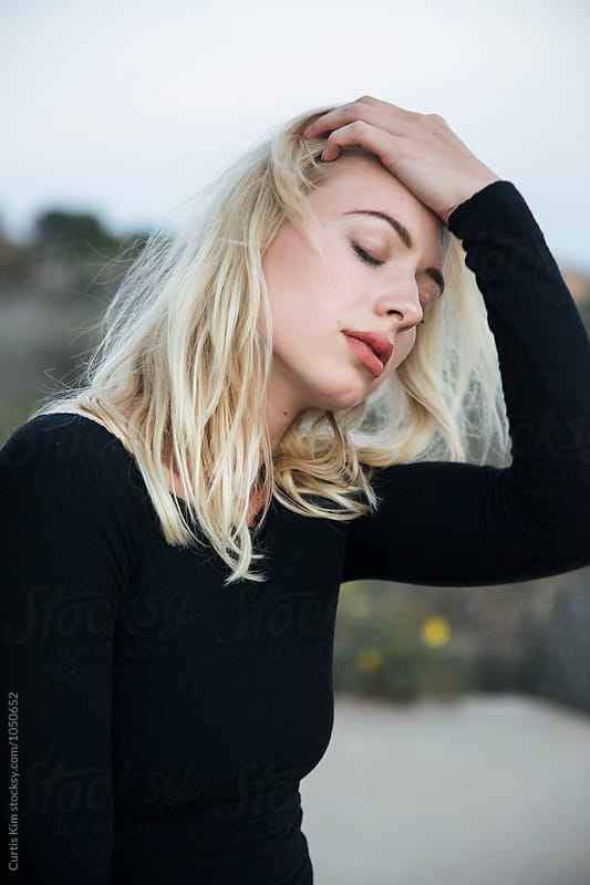 Blonde woman holding hair with eyes closed by Curtis Kim for Stocksy United