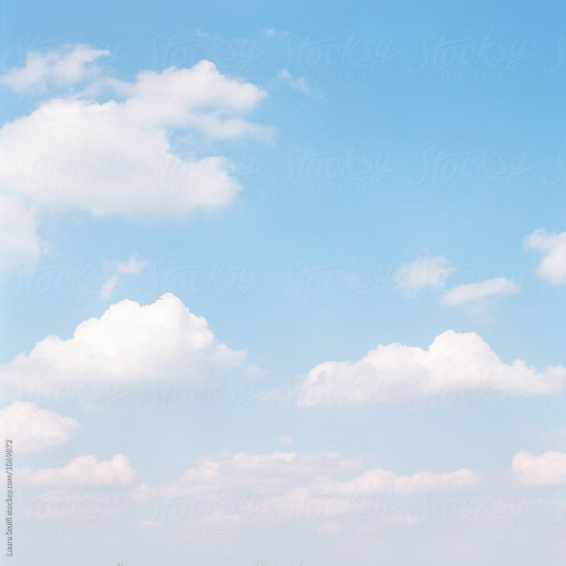 cotton wool clouds float in pale blue sky by Laura Stolfi for Stocksy United