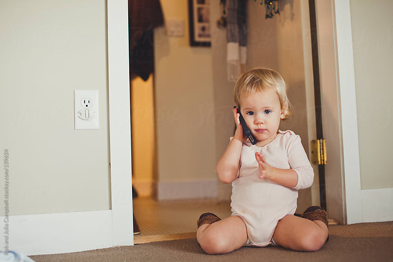 Cute toddler girl talking on mobile cell phone by Rob and Julia Campbell for Stocksy United