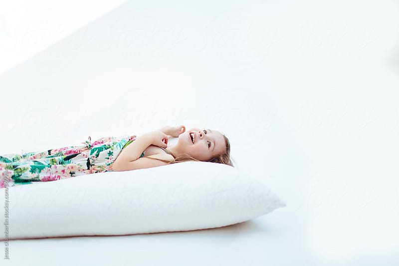 Girl Lays on Pillow by jesse chamberlin for Stocksy United