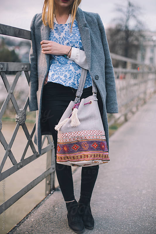 Young fashionable woman walking on the street by Maja Topcagic for Stocksy United