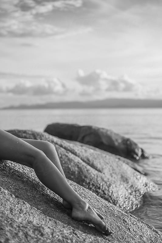 Womans legs on the stone beach by the sea. by Studio Firma for Stocksy United