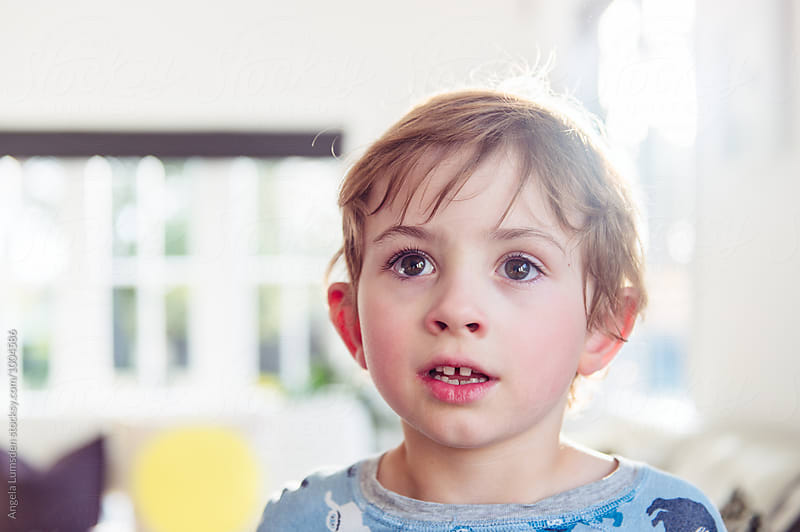 Portrait of a small boy in evening sunlight inside  by Angela Lumsden for Stocksy United