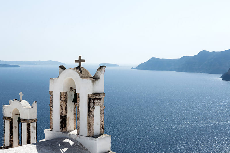 Church bell tower looking out across the caldera of Santorini by Paul Phillips for Stocksy United