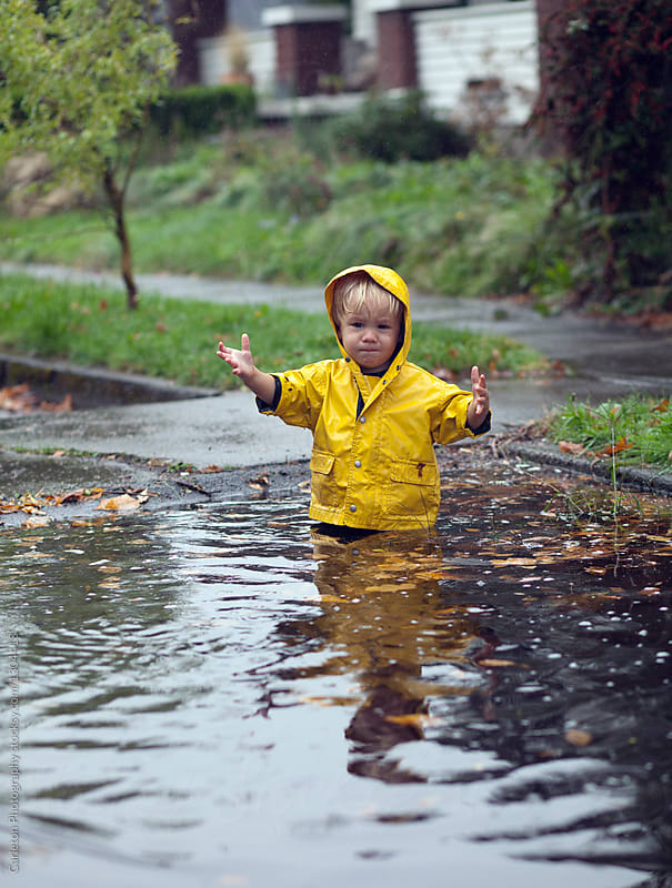19-month-old boy in yellow rain jacket fell in a puddle on a rainy day in Portland, Oregon