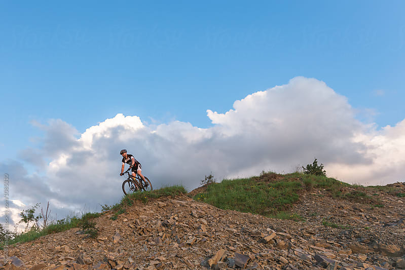 Man on top of hill riding MTB by RG&B Images for Stocksy United