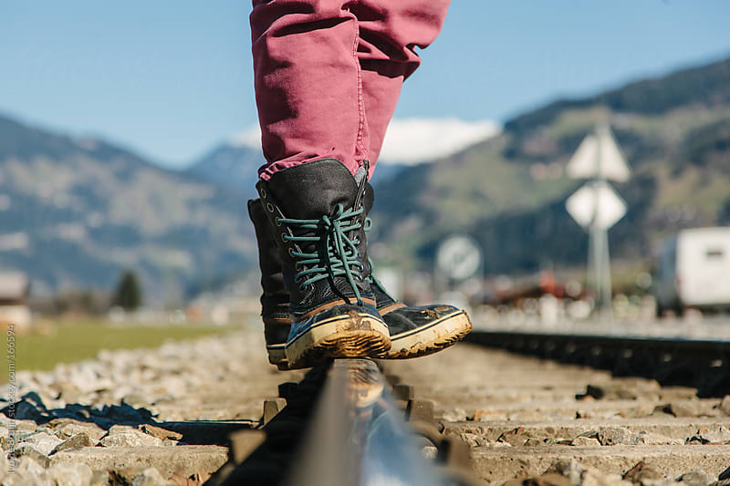 Close up of boots on a train track in the mountains by Ivo de Bruijn for Stocksy United