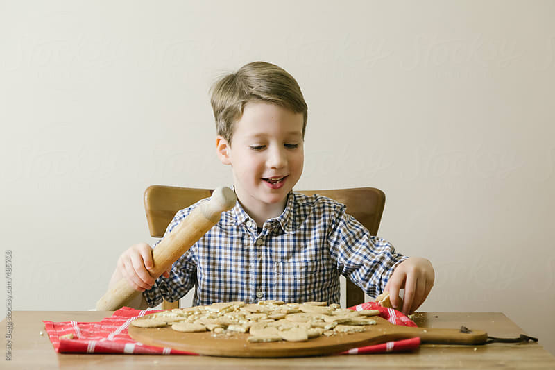 Boy enjoys smashing up biscuits by Kirsty Begg for Stocksy United