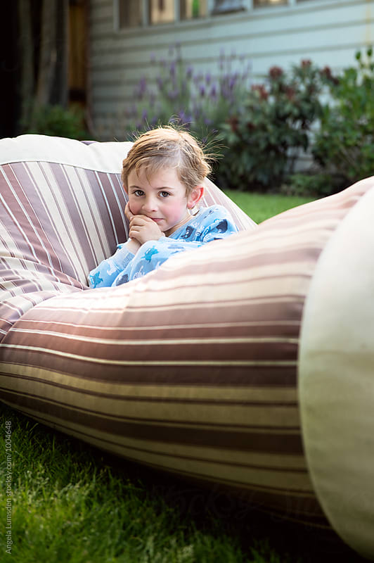 Boy sitting on a large beanbag in the garden in the evening by Angela Lumsden for Stocksy United