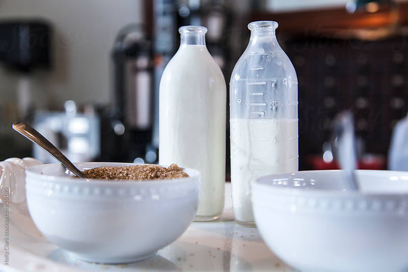 Cream in vintage bottles and sugar in pretty bowls sit on a countertop in a coffee shop. by Holly Clark for Stocksy United