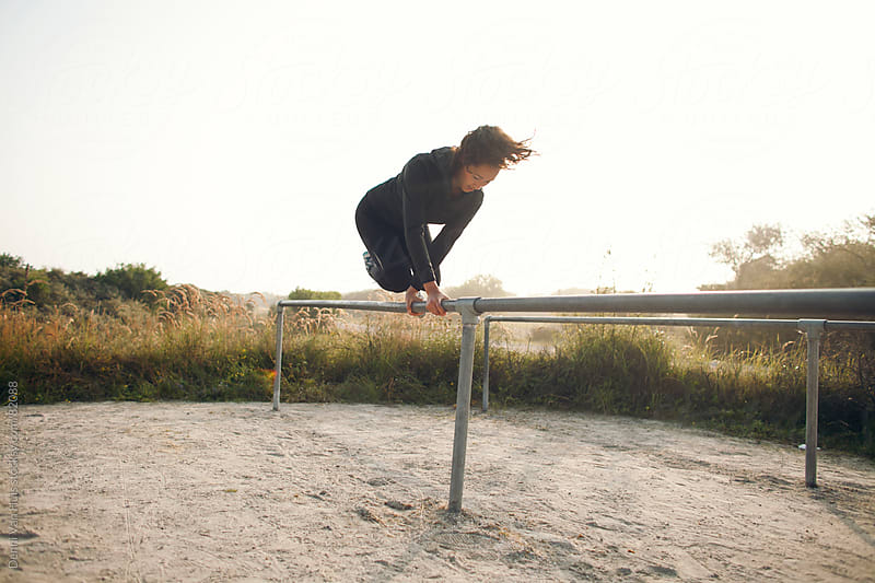 Healthy young woman jumping over a fence as part of her workout by Denni Van Huis for Stocksy United