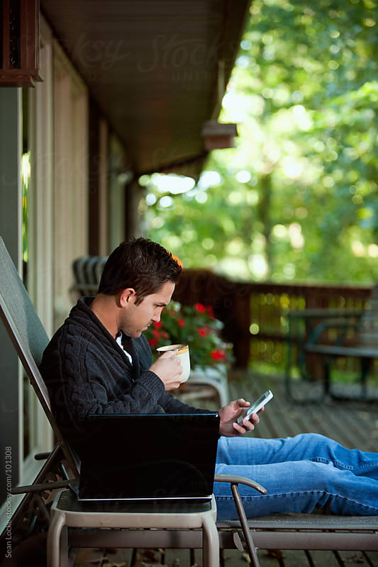 Working: Man Takes Break From Laptop To Check Text Messages by Sean Locke for Stocksy United