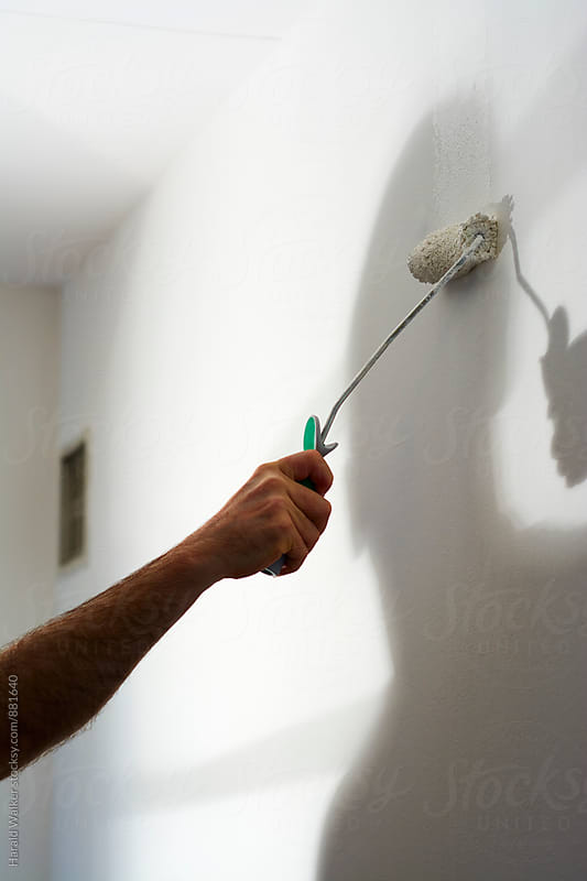 Man painting a wall in a room by Harald Walker for Stocksy United