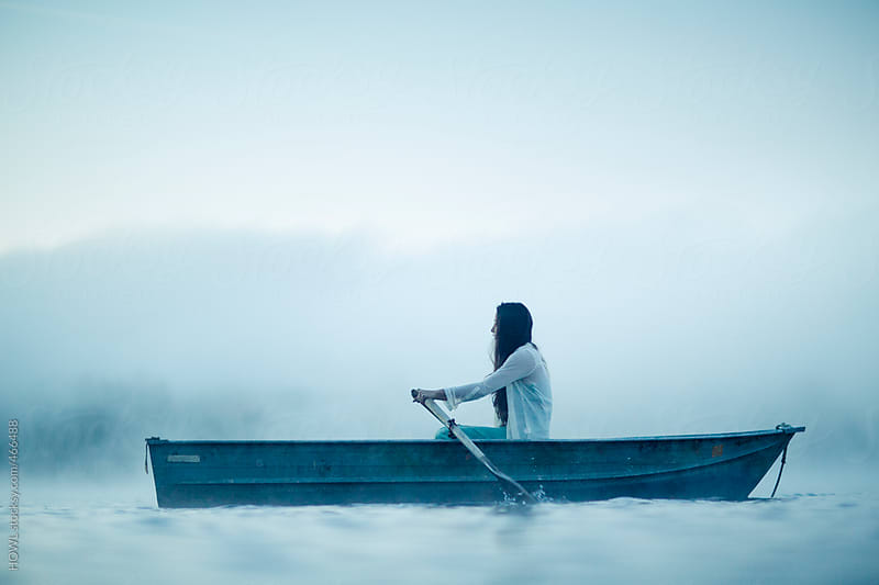 Mysterious woman in row boat on a foggy New England Morning by HOWL for Stocksy United
