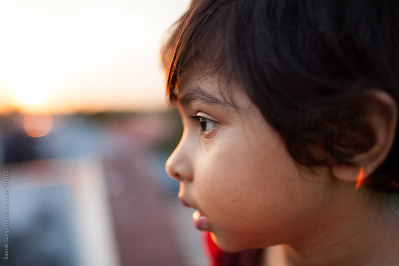 Close up portrait of cute little girl at sunset in a pensive mood by Saptak Ganguly for Stocksy United